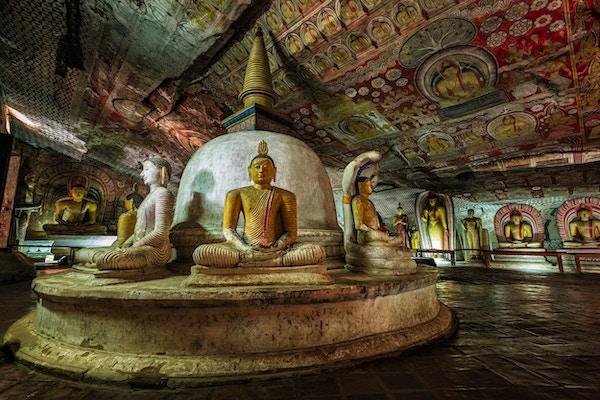 Buddha-statue inne i Dambulla-huletempelet, Sri Lanka. Dambulla huletempel også kjent som Golden Temple of Dambulla er et verdensarvsted på Sri Lanka, som ligger i den sentrale delen av landet. Dette stedet ligger 148 km øst for Colombo og 72 km nord for Kandy. Det er det største og best bevarte huletempelkomplekset på Sri Lanka. Dette tempelkomplekset kan dateres tilbake til det første århundre f.Kr. Det er mer enn 80 dokumenterte grotter i området rundt. De viktigste attraksjonene er spredt over 5 huler, som inneholder statuer og malerier. Disse maleriene og statuene er relatert til Lord Buddha og hans liv. Det er totalt 153 Buddha-statuer, 3 statuer av srilankanske konger og 4 statuer av guder og gudinner.