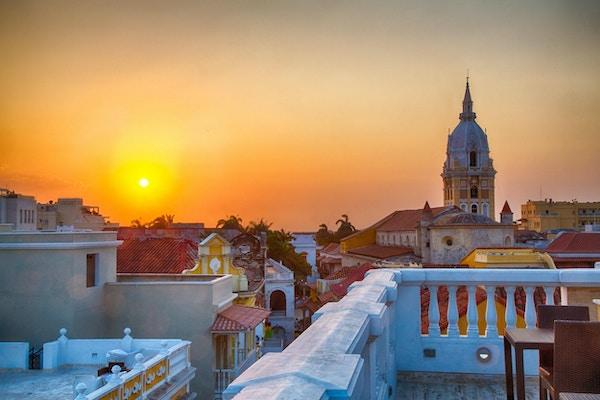 Utsikt over hustakene i den gamle byen Cartagena under en levende solnedgang. Spiret til Cartagena katedral står høyt og stolt.