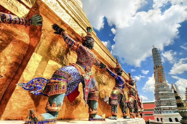 """""""Yaksha som støtter gylden chedi-statue. Gylden pagode ved Wat Phra Kaew. Statuene av Demon - Guardians (Giant) beskyttet gylden pagode i The Emerald Buddha Temple (Wat Phra Kaeo) Grand Palace, Bangkok, Thailand. Vakkert skyer og blå himmel over gyldne Pagoda. Bangkok, Thailand.Se flere bilder som dette på: """""""