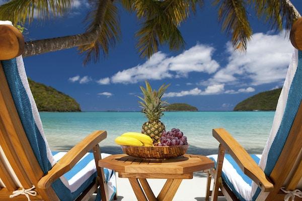 to hvilestoler med teak og et bord fullt av eksotisk frukt på et tropisk karibisk badeby