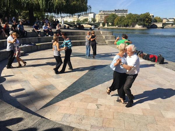 Folk danser tango ved Seinen i Paris