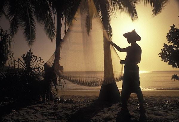 Lokal mann henger opp fiskegarnet i solnedgangen