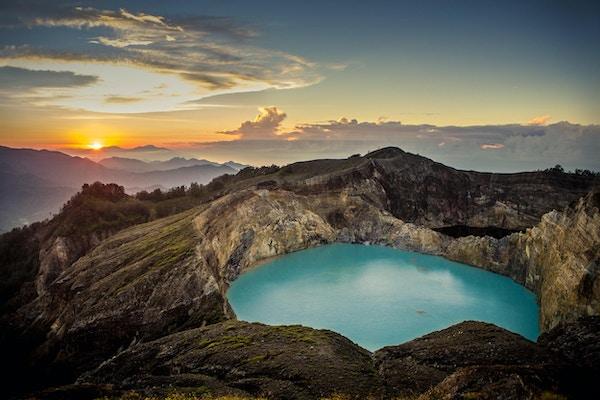 Soloppgang på toppen av vulkanen Kelimutu ved Flores, Indonesia. På fronten kan du se den vakre vannfargede kratersjøen i vulkanen