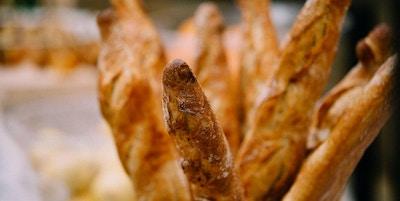 Rader med ferske, bakte franske brød klare til å selges i bakerikurv