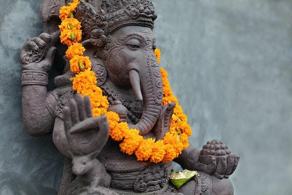 Ganesha med balinesiske Barong-masker som sitter foran tempelet. Dekorert for religiøs festival av oransje blomsterhalskjede og seremonitilbud. Reisebakgrunn, Bali øykunst og kultur.