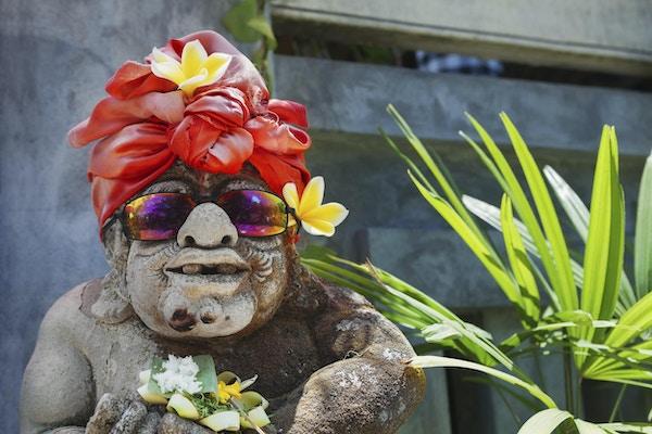 Humoristisk ansiktsportrett av gammel tradisjonell balinesisk tempelvaktstatue kledd i morsomt turistdrakt med solbriller Kunst, kultur fra Bali og indonesiske mennesker og asiatisk feriereiserbakgrunn