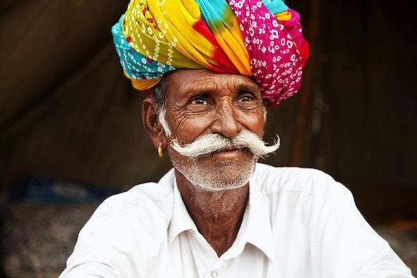 Eldre mann sitter å smiller til kamera