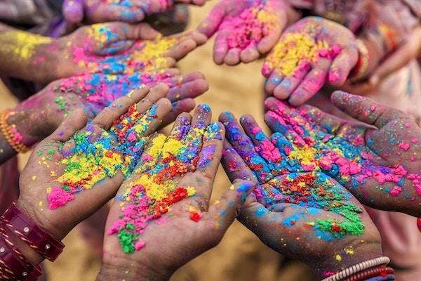 Gruppe av indiske barn som leker lykkelig holi i Rajasthan, India. Indiske barn holder hendene opp og viser fargerike pulver. Holi, festivalen for farger, er en religiøs festival i India, feiret med fargepulver i løpet av våren.