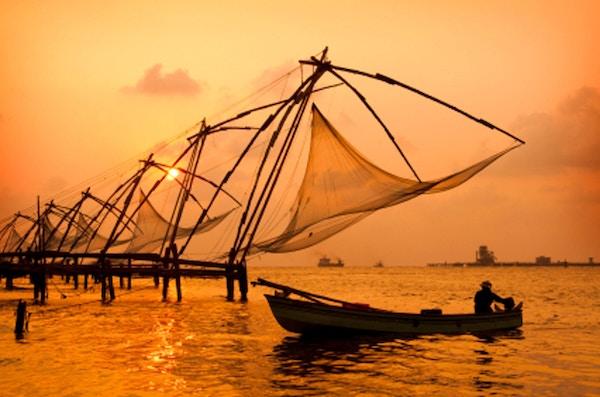 Solnedgang over kinesiske fiskegarn og båt i Cochin (Kochi), Kerala, India.