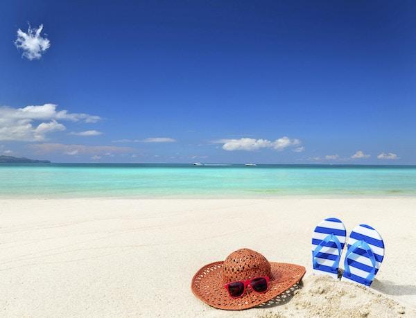 Solhatt med solbriller og tøfler på solrik strand