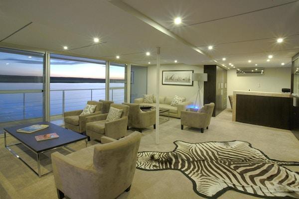 Skipssalong med sebrateppe på gulvet, bord, store panoramavinduer. Foto.