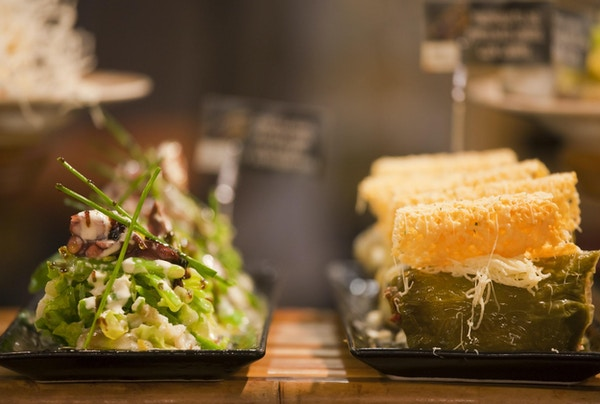 """Spanske Tapas, eller, i Baskerland, Pintxos, uttales """"Pinchos"""" i foodie-hovedstaden i Spania, San Sebastian, på en bar i Mercado La Brexta-matmarkedet. På venstre side, blekksprut salat og grønnsaker, og til høyre, Green Pepper fylt med kjøtt."""