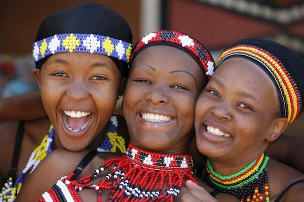 Tre unge Zulu-venninner, kledd i tradisjonelle Zulu-klær, poserer lykkelig for kameraet. Zulu-stammen finnes hovedsakelig i Kwazulu-Natal, Sør-Afrika.