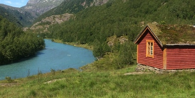 Asurfarget elvevann og en gammel trehytte i Mørkrisdalen