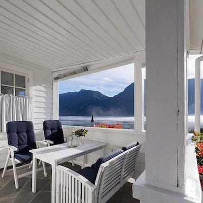 Terrasse med stoler og utsikt mot fjord
