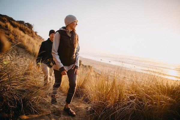 Et par utforsker en strand i Oregon delstaten og nyter den vakre solnedgangen på den nordvestlige kysten i Stillehavet. De går opp en sanddyne, havet synlig i bakgrunnen.