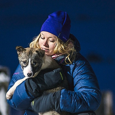 En kvinne som holder en hundevalp