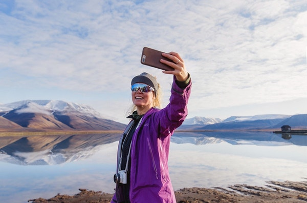 En kvinnelig turist som tar selfie med fjell i bakgrunnen