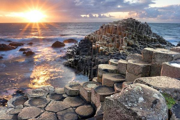 Folk som besøker Giant's Causeway ved solnedgangen i Nord-Antrim, Nord-Irland