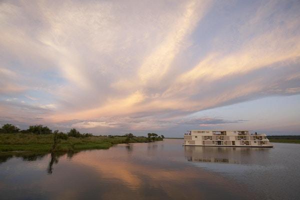 Skip på elven i solnedgang. Foto.