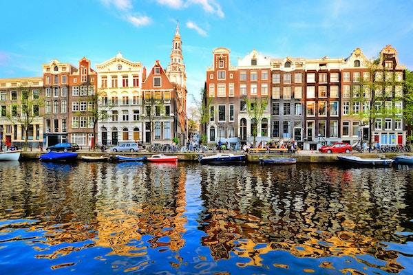 Kanalhus av Amsterdam i skumringen med livlige refleksjoner, Nederland