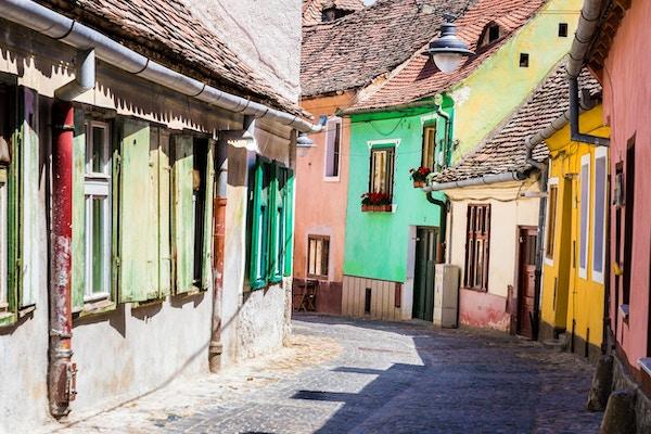 Gamle fargerike hus og hytter i brosteinsbelagte gate, Sibiu, Transylvania, Romania. Sibiu er en by i Transylvania, Romania, med en befolkning på 147.245. Hotellet ligger omtrent 215 km nordvest for Bucuresti, og ligger rundt Cibin-elven, en sideelv til elven Olt. Nå var hovedstaden i Sibiu County, mellom 1692 og 1791 og 1849-1865 Sibiu hovedstad i fyrstedømmet Transylvania. Horisontalt fargebilde med kopieringsplass.