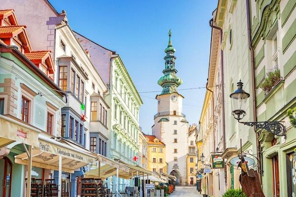 Arkivfotografi av en bakgate med butikker og restauranter i gamlebyen i Bratislava, Slovakia.