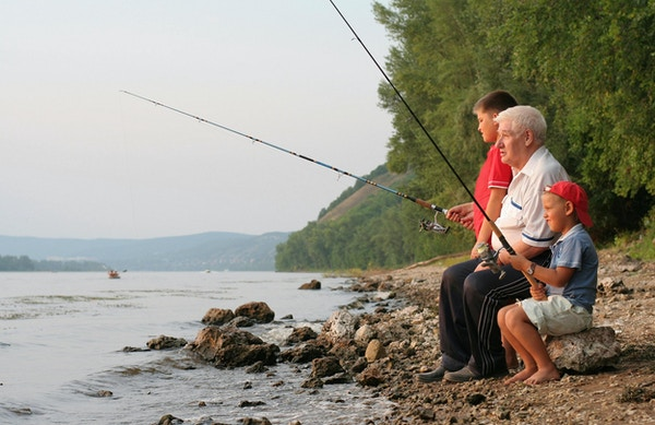 En gråhodet bestefar med to barnebarn på fiske