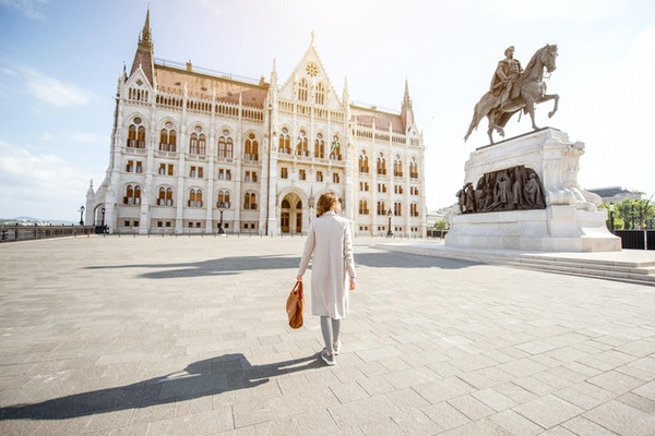 Kvinne som går på plassen nær den berømte parlamentsbygningen under mornignlyset i Budapest, Ungarn