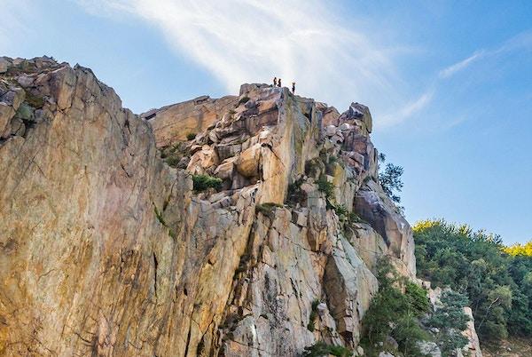 Mennesker på toppen av stupbratt klippe