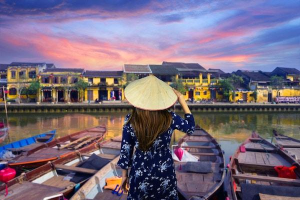 Kvinneturist har tradisjonell vietnamesisk Non La-hatt og ser på vakker utsikt ved elvebredden i gamlebyen Hoi An i Vietnam under solnedgangsskumring.