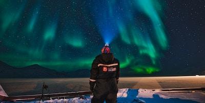En turist som nyter synet av nordlyset som danser på himmelen