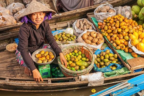 Vietnamesisk, kvinnelig fruktselger på flytende marked, som selger frukt fra båten sin i Mekong-elvedeltaet, Vietnam.
