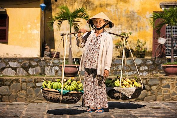 Vietnamesisk kvinne som bærer frukt til salgs i Hoi An, Vietnam.