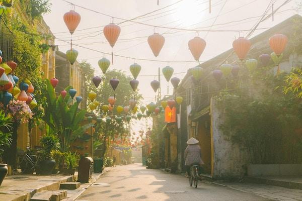Ung kaukasisk kvinne som går i Hoi An by om morgenen