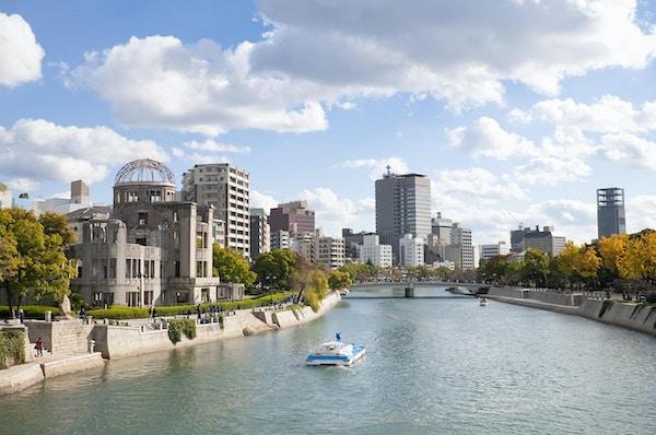 Høstfarger langs elvebankene til Ota-elven i det sentrale Hiroshima. Til venstre ligger UNESCOs beskyttede Atombombe-domkirke, som lå nært detoneringen av atombomben som falt den 6. august 1945. Bygningen har med intensjon blitt stående ureparert siden 1945.