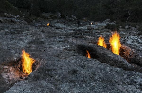 Brannene til Yanartas (flammende stein) om natten, Antalya, Tyrkia. små branner som stadig brenner fra ventiler i steinene på siden av fjellet. Området ligger på et spor som er populært blant turgåere og vandrere på Lycian Way.