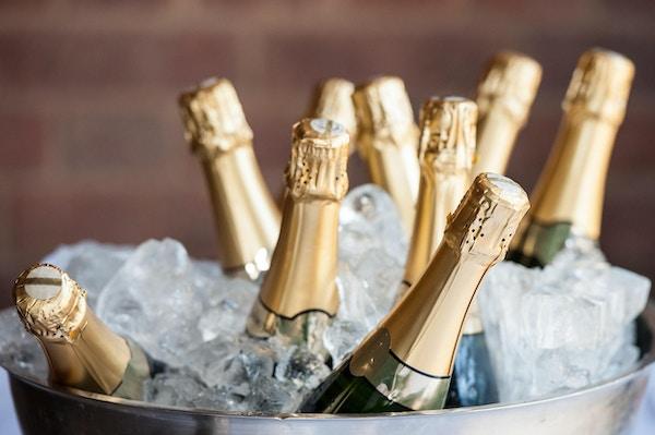 Champagneflaske i en bøtte med is.