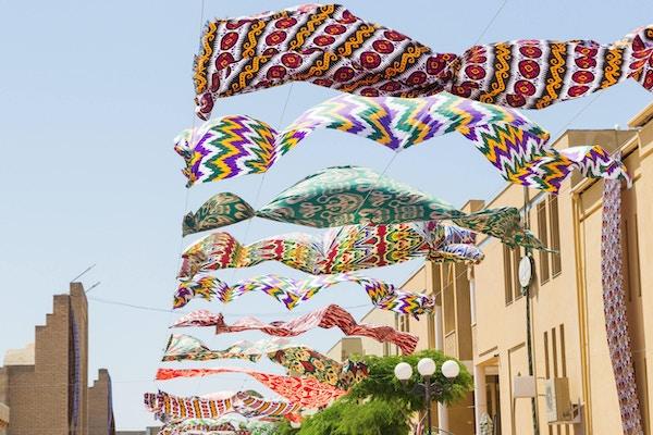 Flerfargede tekstilmaterialer i silke som flagrer mot den blå himmelen i Margilan.