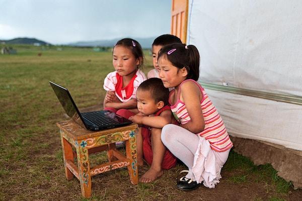 Mongolske barn som bruker en laptop med et mongolsk telt i bakgrunnen