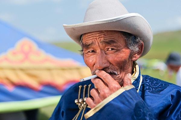 Mongolsk mann i nasjonal klesdrakt under Naadam-festivalen, Sentrale Mongolia. Naadam er den mest sette festivalen blant mongoler, og antas å ha eksistert i århundrer i en eller annen form. Naadam har sitt opphav i aktiviteter som for eksempel militære parader og sportslige konkurranser som bueskyting, ridning og bryting, som fulgte med i feiringen ved forskjellige anledninger.