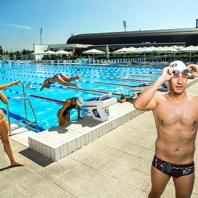 Utendørs svømmebasseng med mange svømmere