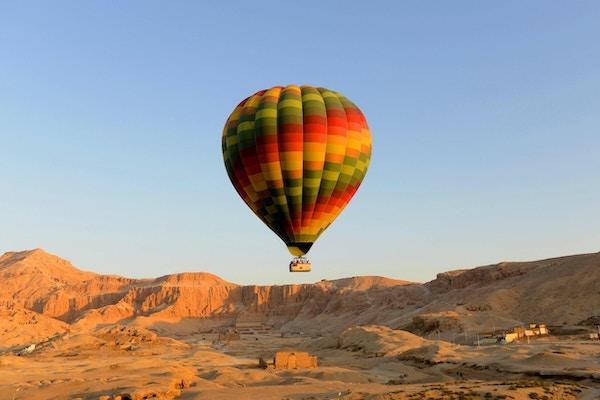 Luftballong som løfter av i luxor Egypt med templet til hatshepsut i bakgrunnen