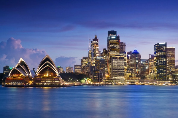 Operahuset i Sydney og Circular Quay-distriktet, sett under en purpuraktig himmel i skumringen.