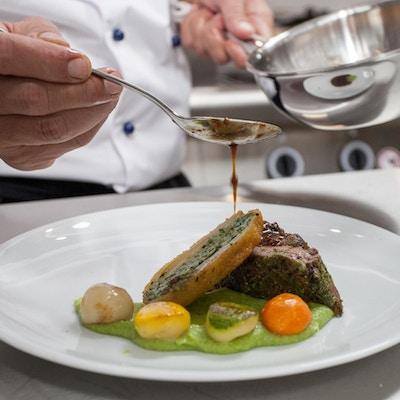 Nærbilde av kjøttrett og kokk som heller saus over.