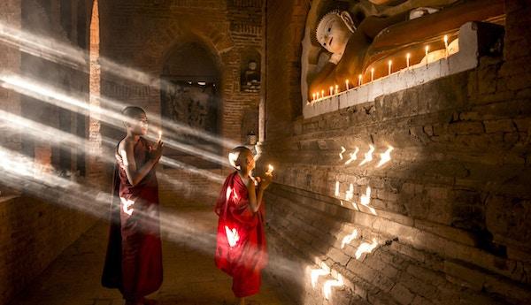 To unge buddhistiske munker som ber inne i tempelet i Bagan, Myanmar