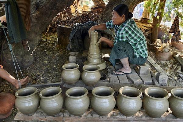 Kvinne sittende på huk i tradisjonelle klær som lager leirkrukker. Foto.