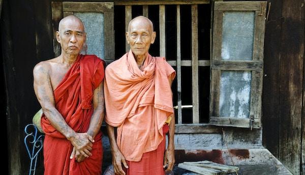 To burmesiske munker i 70-årene står sammen på verandaen til klosteret sitt i Mandalay, Myanmar