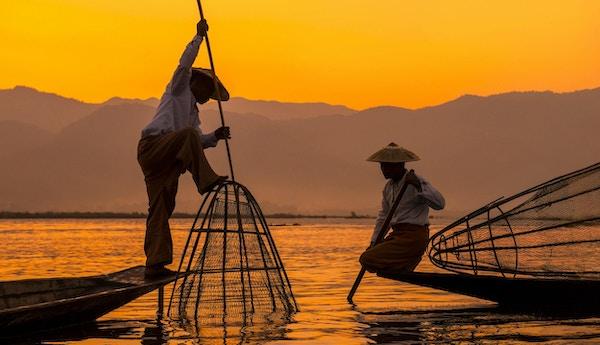 To fiskere i vakker solnedgang ved innsjøen Inle, Myanmar