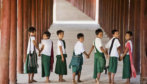 Syv små barn smiler i kamera mens de er på vei til skolen